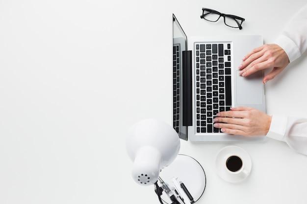 Vista superiore delle mani sul computer portatile allo scrittorio del lavoro con lo spazio della copia