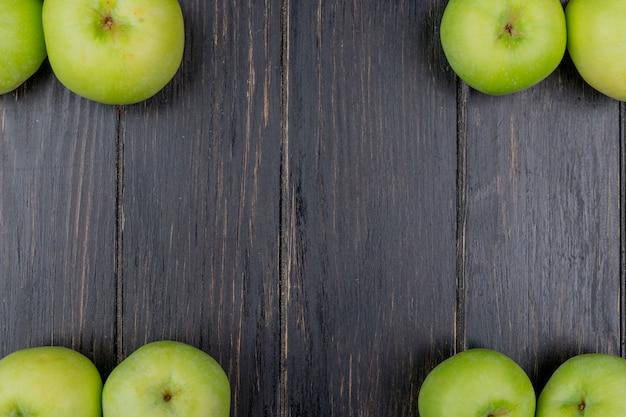 Vista superiore delle mele verdi su fondo di legno con lo spazio della copia