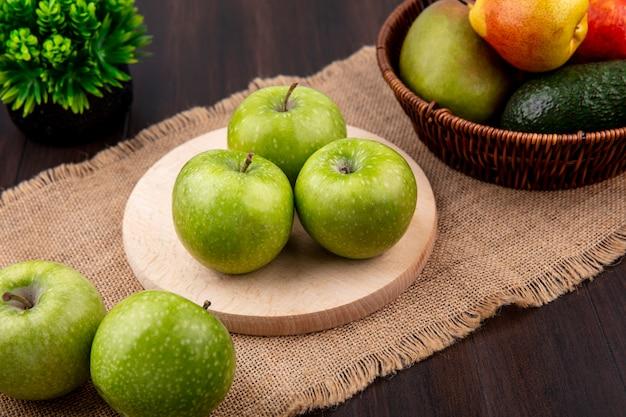 Vista superiore delle mele verdi su un bordo di legno della cucina sul panno di sacco su superficie di legno