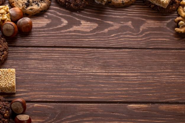 Vista superiore delle noci e dei biscotti con lo spazio della copia su un di legno