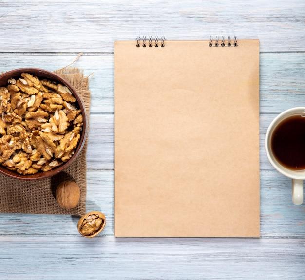 Vista superiore delle noci in uno sketchbook di ciotola e una tazza con tè su un legno