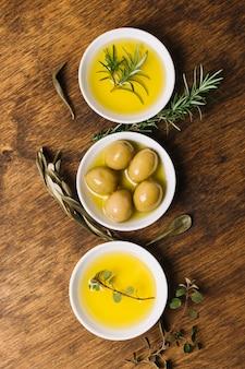Vista superiore delle olive e dell'olio con ciotole disposte di rosmarino