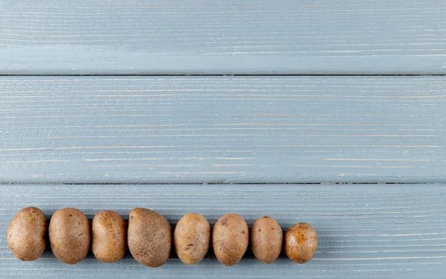 Vista superiore delle patate dalla parte di sinistra su fondo di legno con lo spazio della copia