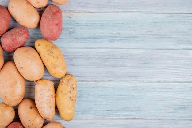 Vista superiore delle patate gialle e rosse bianche ruggine dalla parte di sinistra e dalla superficie di legno con lo spazio della copia