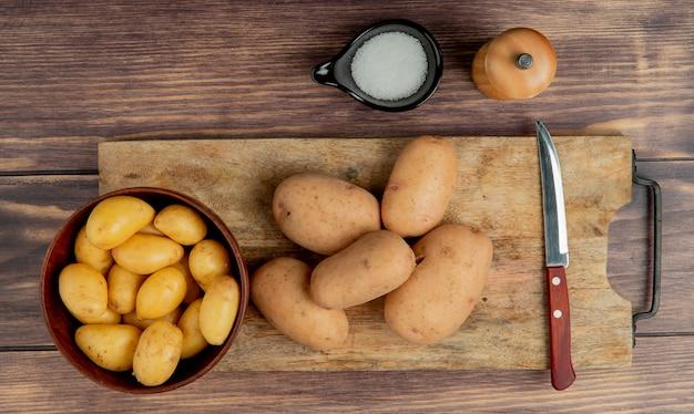 Vista superiore delle patate in ciotola e sul tagliere con coltello e sale su superficie di legno