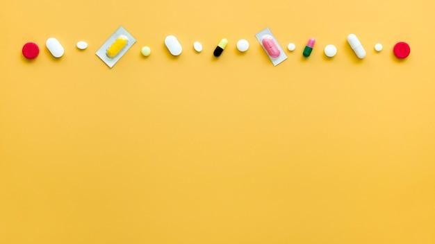 Vista superiore delle pillole differenti nella fila con lo spazio della copia