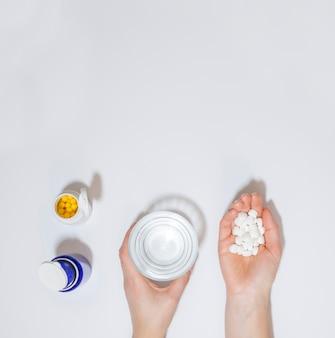 Vista superiore delle pillole e del bicchiere d'acqua della tenuta della mano