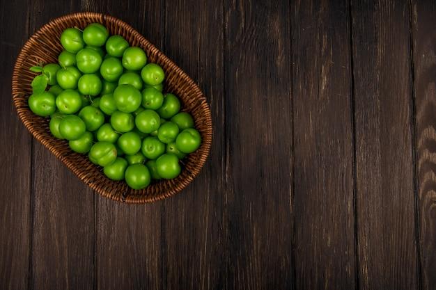 Vista superiore delle prugne acide verdi in un canestro di vimini sulla tavola di legno scura con lo spazio della copia