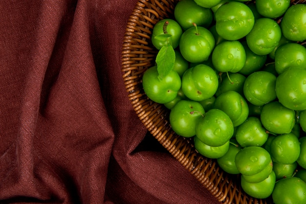 Vista superiore delle prugne acide verdi in un cestino di vimini sulla tabella rosso scuro del tessuto con lo spazio della copia
