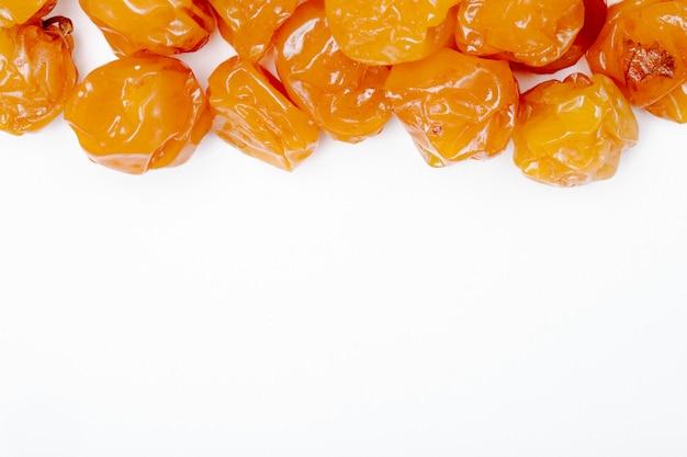Vista superiore delle prugne ciliegia secche su fondo bianco con lo spazio della copia