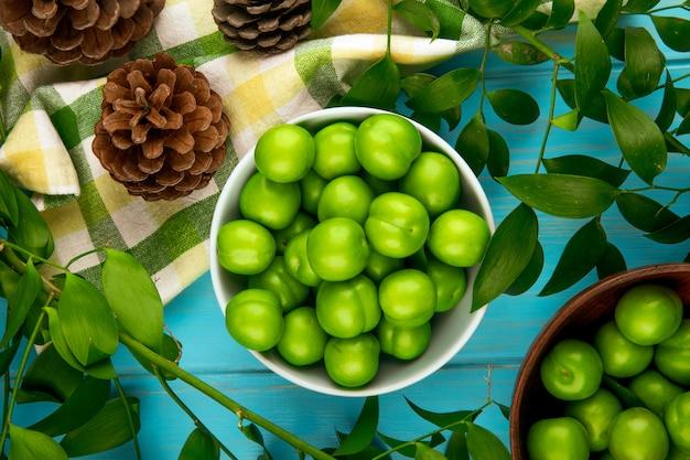 Vista superiore delle prugne verdi acide in una ciotola e dei coni con le foglie del rusco sulla tavola di legno blu