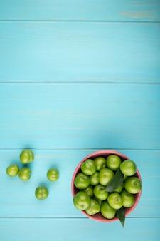 Vista superiore delle prugne verdi acide in una ciotola sulla tavola blu con lo spazio della copia