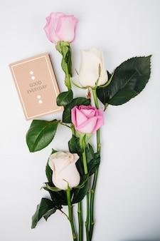 Vista superiore delle rose rosa e bianche di colore con la piccola cartolina isolata su fondo bianco