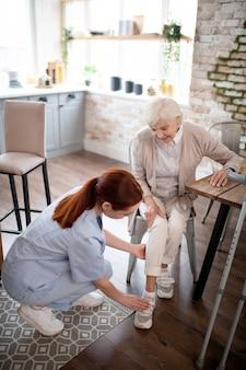 Vista superiore delle scarpe da allacciatura dai capelli rossi dell'infermiera per il paziente