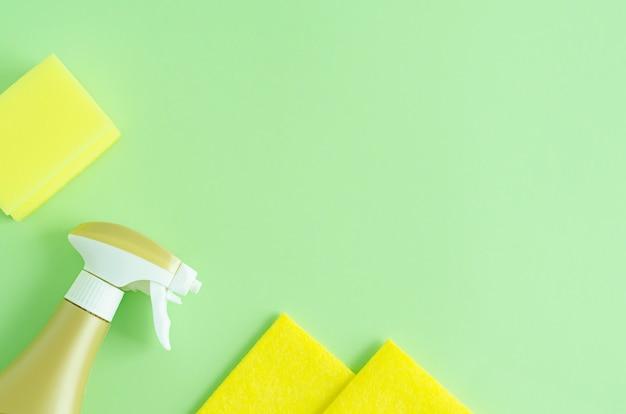 Vista superiore delle spugne gialle di lavaggio e della bottiglia dello spruzzo per la pulizia sul verde