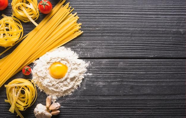 Vista superiore delle tagliatelle e pasta degli spaghetti crudi con gli ingredienti sulla plancia di legno