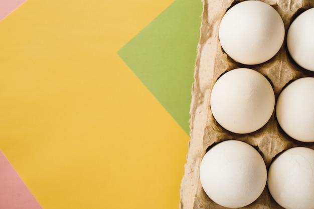 Vista superiore delle uova bianche del pollo in un cartone aperto dell'uovo su fondo variopinto. copia spazio. cibo sano naturale e concetto di agricoltura biologica. uova in confezione