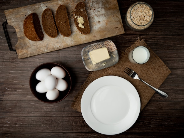 Vista superiore delle uova con il piatto di pane nero affettato della forcella vuota del piatto del latte di burro e il barattolo dei fiocchi di avena su fondo di legno