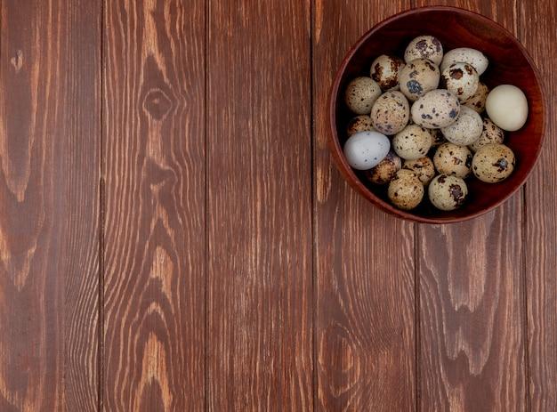 Vista superiore delle uova di quaglia con le coperture color crema con le macchie marroni su un fondo di legno con lo spazio della copia
