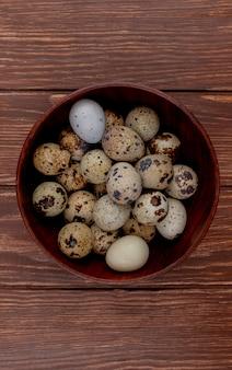 Vista superiore delle uova di quaglia con le coperture color crema con le macchie marroni su una ciotola di legno su un fondo di legno