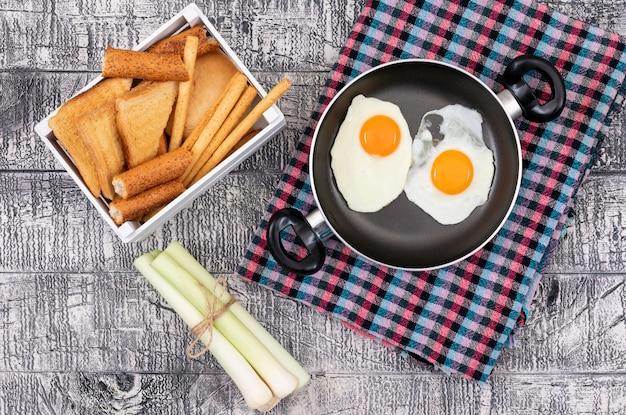 Vista superiore delle uova fritte con i pani tostati sull'orizzontale di superficie di bianco
