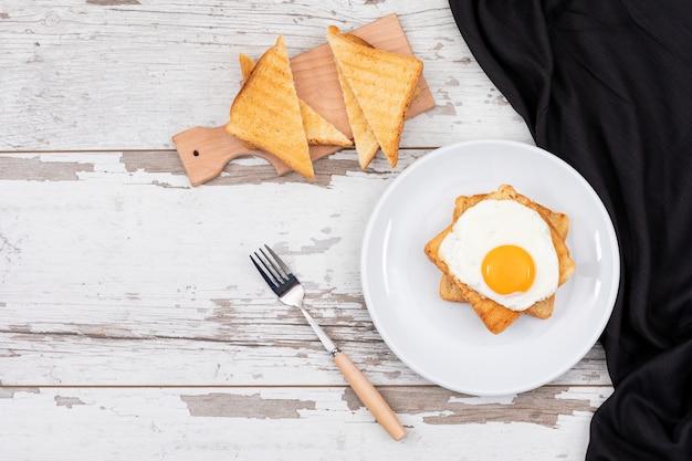 Vista superiore delle uova fritte della prima colazione sul piatto bianco con pane tostato e spazio della copia sull'orizzontale di superficie di legno