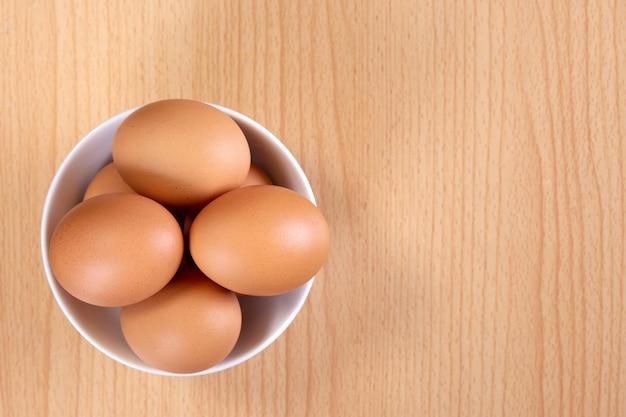 Vista superiore delle uova in ciotola su di legno