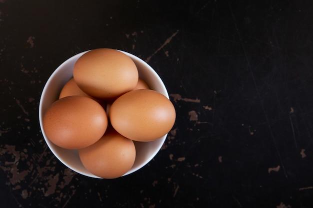 Vista superiore delle uova in ciotola sul nero