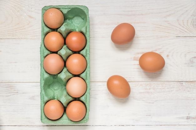 Vista superiore delle uova marroni crude del pollo in contenitore di cartone dell'uovo