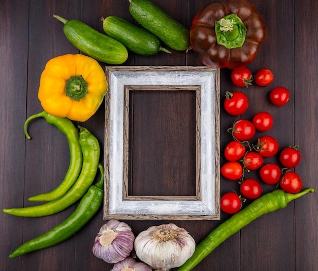 Vista superiore delle verdure come aglio del cetriolo del pomodoro del pepe intorno alla struttura su superficie di legno