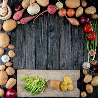 Vista superiore delle verdure come aglio della cipolla del ravanello dello scalogno con sedano e patata tagliati sul tagliere su fondo di legno con lo spazio della copia
