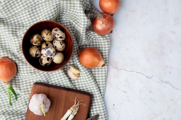 Vista superiore delle verdure come aglio della cipolla dell'uovo sul panno su fondo bianco con lo spazio della copia