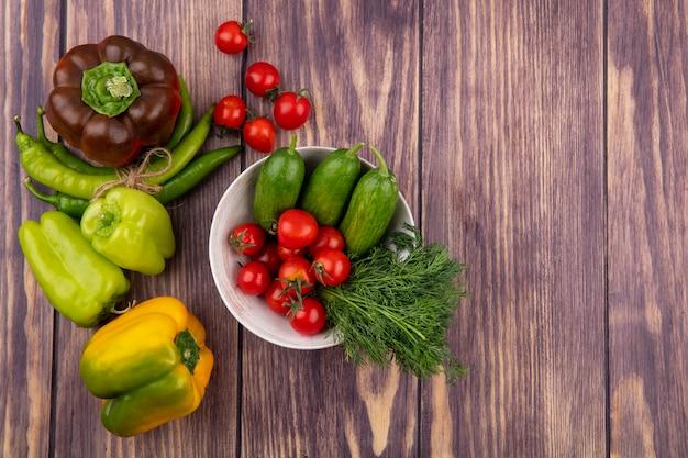 Vista superiore delle verdure come aneto del cetriolo del pomodoro in ciotola con i peperoni su superficie di legno