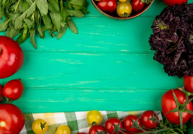 Vista superiore delle verdure come basilico verde del pomodoro delle foglie di menta su verde con lo spazio della copia