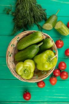 Vista superiore delle verdure come cetriolo e pepe in ciotola con aneto di pomodoro intorno su superficie verde