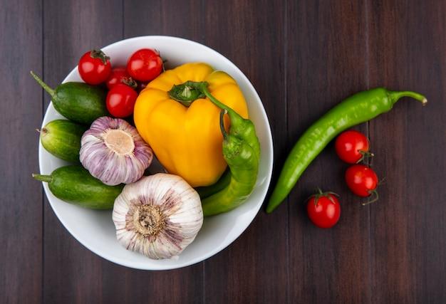 Vista superiore delle verdure come cetriolo e pomodoro del pepe di aglio in ciotola su superficie di legno