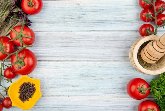 Vista superiore delle verdure come coriandolo del pomodoro con il frantoio dell'aglio del pepe nero dai lati destro e sinistro e superficie di legno con lo spazio della copia