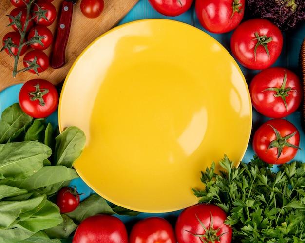 Vista superiore delle verdure come coriandolo del pomodoro del basilico degli spinaci con il coltello sul tagliere e piatto vuoto su superficie blu
