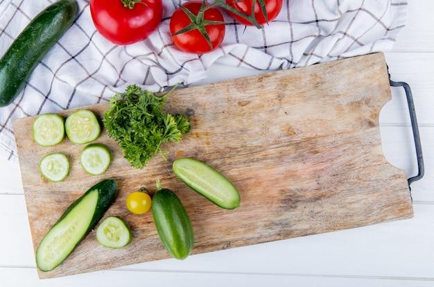 Vista superiore delle verdure come coriandolo del pomodoro del cetriolo sul tagliere con il cetriolo e pomodori sul panno e sul legno