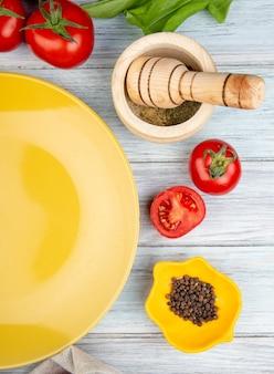Vista superiore delle verdure come foglie di menta verdi del pomodoro con il frantoio dell'aglio dei semi del pepe nero e piatto vuoto su legno
