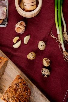 Vista superiore delle verdure come lo scalogno dell'aglio dell'uovo con pane nero sul fondo di borgogna