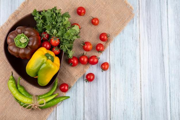 Vista superiore delle verdure come mazzo del pomodoro di pepe di coriandolo in ciotola e su tela di sacco su superficie di legno