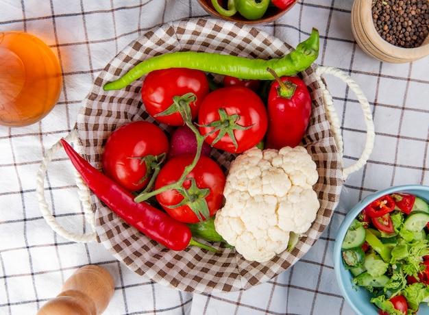 Vista superiore delle verdure come merce nel carrello del cavolfiore del ravanello del pomodoro del pepe con l'insalata di verdure del pepe nero del burro sul fondo del panno del plaid