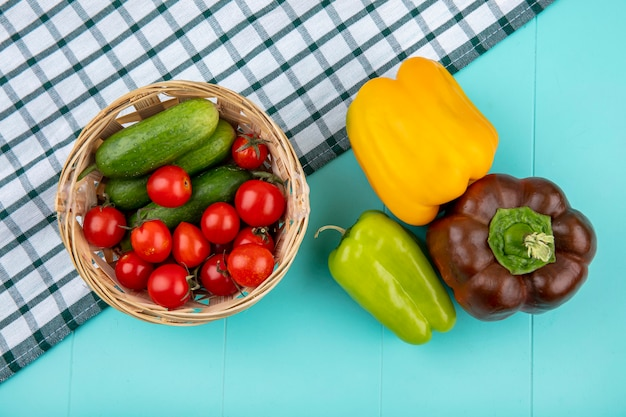 Vista superiore delle verdure come merce nel carrello del cetriolo del pomodoro sul panno e sui peperoni del plaid su superficie blu