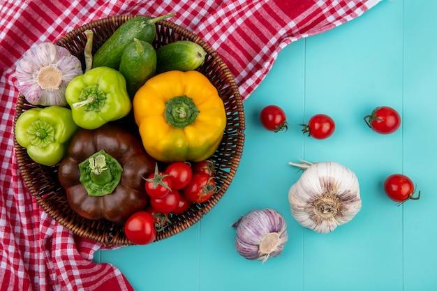 Vista superiore delle verdure come merce nel carrello del pomodoro dell'aglio del cetriolo del pepe sul panno del plaid e sulla superficie del blu