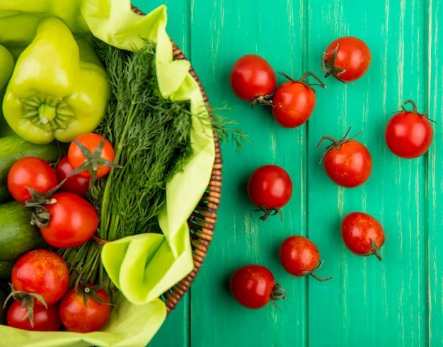 Vista superiore delle verdure come merce nel carrello dell'aneto del cetriolo del pomodoro del pepe su superficie verde