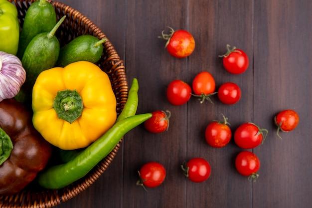Vista superiore delle verdure come merce nel carrello e pomodori del cetriolo del pepe su superficie di legno
