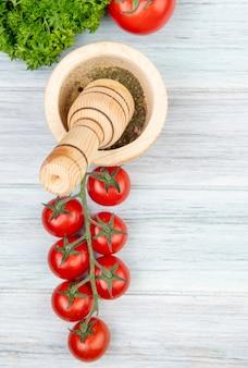 Vista superiore delle verdure come pomodoro del coriandolo con pepe nero in frantoio dell'aglio su superficie di legno