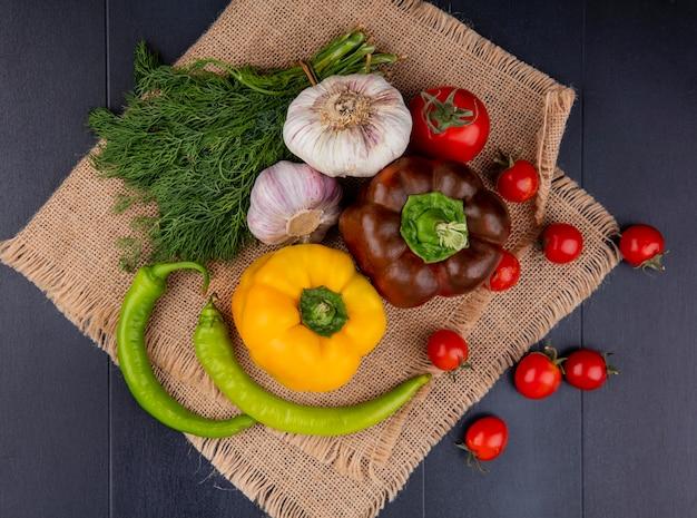 Vista superiore delle verdure come pomodoro dell'aneto dell'aglio di pepe su tela di sacco su superficie nera