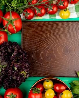 Vista superiore delle verdure come pomodoro verde del basilico delle foglie di menta intorno al vassoio vuoto su superficie verde